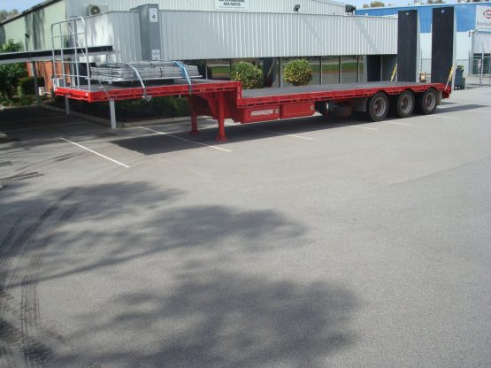 drop deck trailer in red standing in parking lot in front of store front