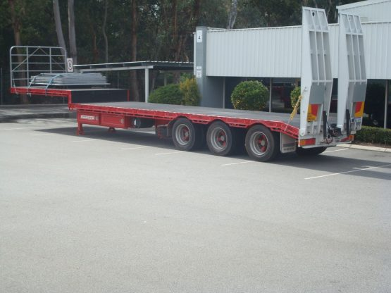 drop deck trailer not hooked onto truck in red standing in parking lot in front of gumtrees with loading tracks hoisted up