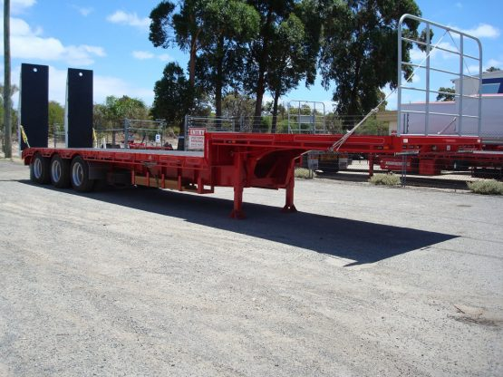drop deck trailer not hooked onto truck in red standing in shop yard