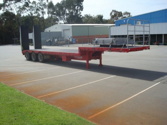 drop deck trailer not hooked onto truck in red standing in parking lot