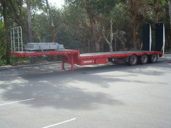 drop deck trailer not hooked onto truck in red standing in parking lot in front of gumtrees.