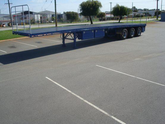 TSE Blue Flat Top Semi trailer side view in parking lot